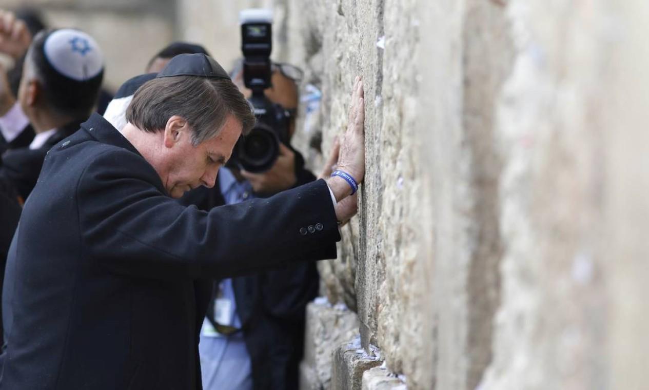 """Em gesto inédito, Bolsonaro reza diante do Muro das Lamentações. Presidente brasileiro foi o primeiro chefe de Estado a visitar o lugar sagrado acompanhado do primeiro-ministro israelense, Benjamin Netanyahu. Israel, que ocupou o setor oriental de Jerusalém em 1967, considera a cidade sua capital """"única e indivisível"""", mas a anexação do setor árabe, onde fica a Cidade Velha, não é reconhecida pela ONU Foto: POOL / REUTERS"""