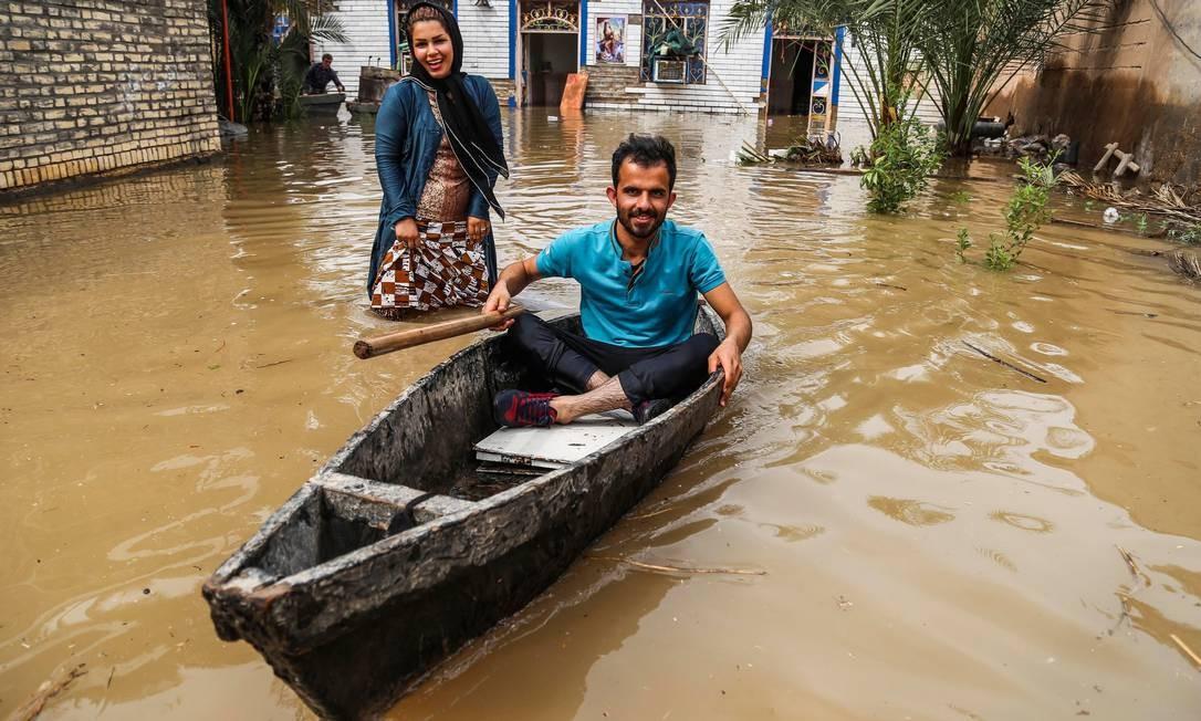 Um iraniano utiliza um barco para se locomover por uma vila ao redor da cidade de Ahvaz, na província de Khuzestan, no Irã. Autoridades iranianas ordenaram a evacuação de pelo menos 13 províncias atingidas por inundações no país, ocorridas após fortes chuvas no fim de março. Ao todo, 23 pessoas morreram e mais de 100 ficaram feridas Foto: - / AFP
