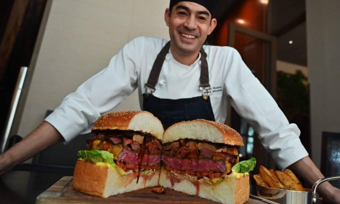 O chefe de cozinha Patrick Shimada, do The Oak Door, do hotel Grand Hyatt, posa com um hambúrguer de 3 quilos, em Tóquio Foto: CHARLY TRIBALLEAU / AFP