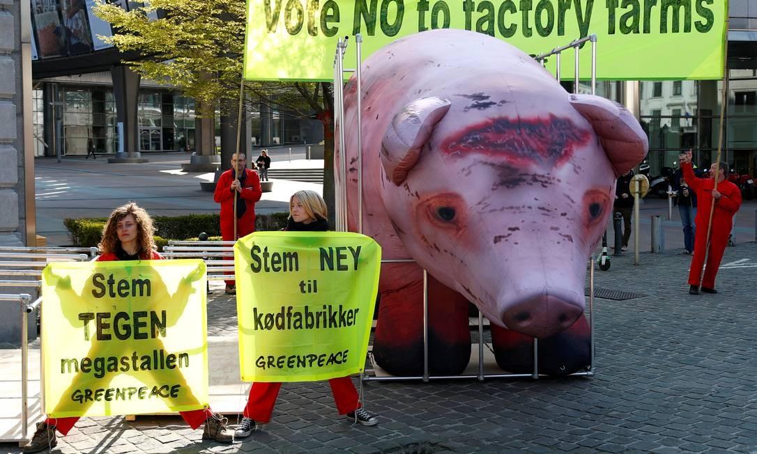 Ativistas do Greenpeace encenam um protesto com um porco inflável em uma jaula, enquanto esperam que o comitê agrícola do Parlamento Europeu vote sobre a Política Agrícola Comum, em Bruxelas, na Bélgica Foto: FRANCOIS LENOIR / REUTERS