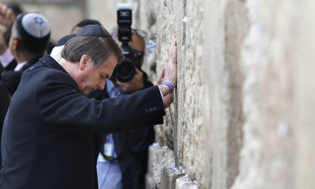 Em gesto inédito, Bolsonaro reza diante do Muro das Lamentações. O presidente brasileiro foi o primeiro chefe de Estado a visitar o lugar sagrado acompanhado do primeiro-ministro israelense, Benjamin Netanyahu Foto: POOL / REUTERS