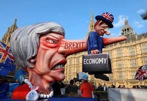 Ativistas contra o Brexit fazem protesto neste 1º de abril em frente ao parlamento britânico, exibindo a primeira-ministra Theresa May com um nariz de mentirosa que 'mata' a economia do país Foto: ISABEL INFANTES/AFP