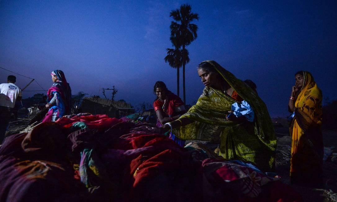 Aaldeões nepaleses procuram pertences nos escombros de casas danificadas na aldeia de Bhaluhi Bharbaliya, no distrito de Bara, no sul do Nepal, perto de Birgunj, na manhã depois de uma tempestade rara de primavera Foto: PRAKASH MATHEMA / AFP