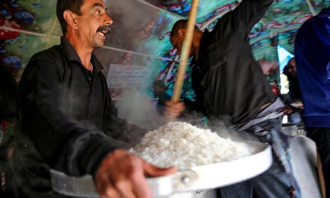 Homens preparam e distribuem alimentos para peregrinos xiitas marchando do centro da capital iraquiana, Bagdá, em direção ao distrito norte de Kadhimiya, enquanto os fiéis se preparam para marcar a semana do aniversário da morte do sétimo Imame xiita, Musa al-Kadhim, no século VIII dC Foto: SABAH ARAR / AFP