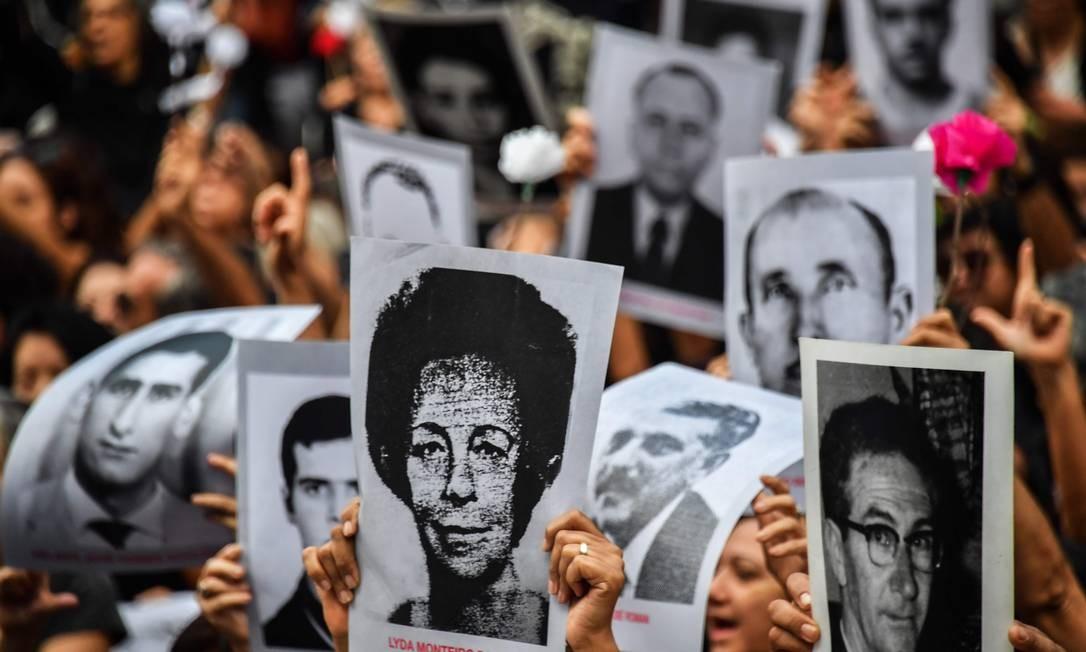 Pessoas carregam fotos de pessoas que morreram ou desapareceram durante a ditadura militar no Brasil, entre 1964 e 1985, no 55º aniversário do golpe militar, no Parque do Ibirapuera, em São Paulo Foto: NELSON ALMEIDA / AFP