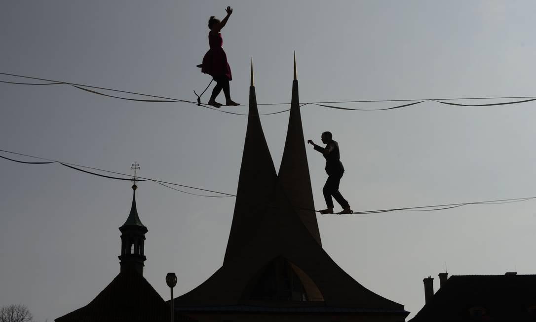 Equilibristas balançam em uma corda em frente ao Monastério de Emmaus, à margem de uma conferência de imprensa do Ministro da Saúde da República Tcheca, apoiando pessoas com doenças mentais, em Praga Foto: MICHAL CIZEK / AFP
