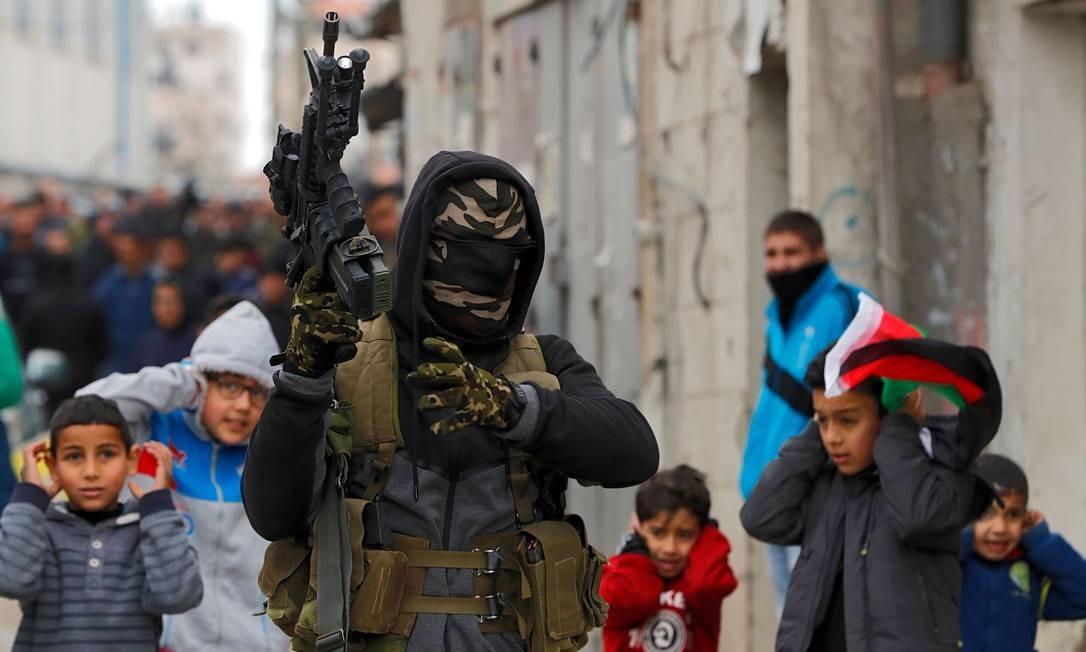 Militantes palestinos erguem metralhadoras enquanto disparam para o ar durante o funeral de um palestino de 23 anos, Mohammed Adwan, morto durante um confronto com forças israelenses perto de Jerusalém durante a noite, no Campo de refugiados de Qalandia, perto de Ramallah, na Cisjordânia Foto: AHMAD GHARABLI / AFP