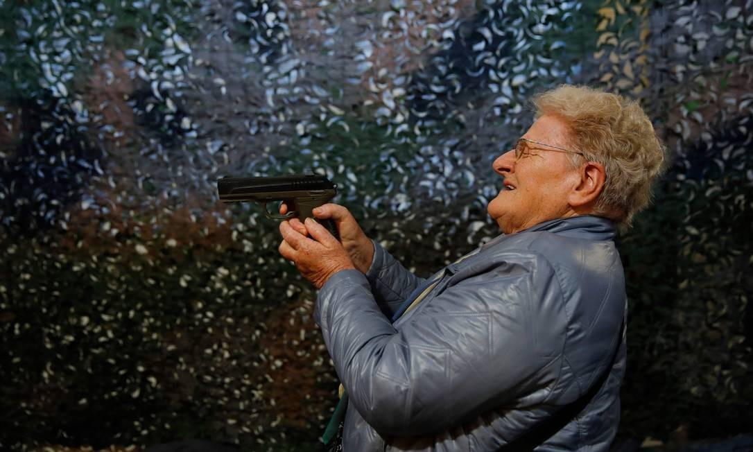 Um visitante testa uma pistola de CO2 durante a 45ª edição da Feira de Armas, em Lucerna, na Suíça. O país possui uma enraizada cultura pró-armas e tem tentado evitar os debates acalorados sobre posse de armas. Um referendo, a ser votado em maio, vai determinar se o país realizará ou não as reformas na legislação sobre posse de armas exigidas pela União Europeia. Foto: STEFAN WERMUTH / AFP