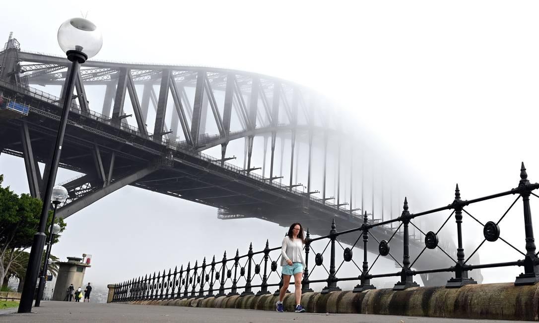 Pessoas caminham perto da Ponte do Porto da Austrália, em Sydney, durante nevoeiro Foto: SAEED KHAN / AFP