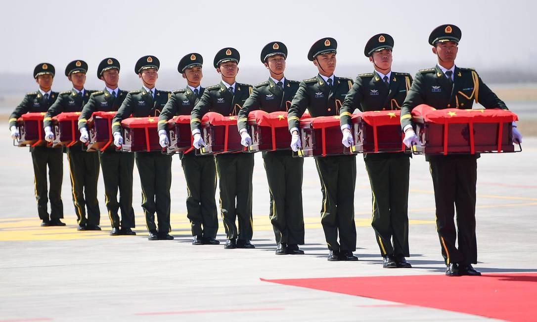 Guardas de honra chineses carregam caixões contendo os restos mortais de soldados chineses no Aeroporto Internacional de Shenyang Taoxian, em Shenyang, na província de Liaoning. Os restos de dez soldados chineses mortos durante a Guerra da Coreia, de 1950 a 1953, foram devolvidos à Coreia do Sul para o enterro permanente Foto: STR / AFP