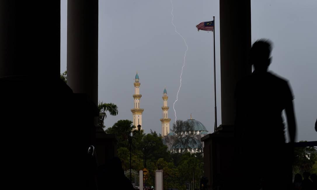 Relâmpago atinge o céu perto de uma mesquita em Kuala Lumpur, na Malásia Foto: MOHD RASFAN / AFP
