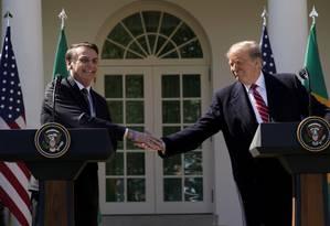 Trump e Bolsonaro se cumprimentam após a coletiva de imprensa conjunta durante a visita do presidente brasileiro aos EUA no mês passado: sem chance de o Brasil se tornar membro da Otan, como o americano sugeriu Foto: Kevin Lamarque/REUTERS/19-03-2019