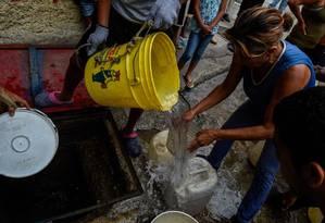 Diante dos apagões e da falta de água, pessoas recorrem a poço em Petare, Caracas Foto: FEDERICO PARRA / AFP