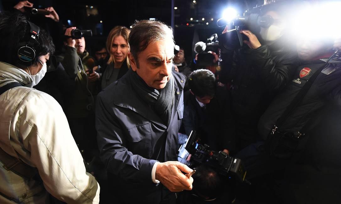 O ex-presidente da Nissan Carlos Ghosn e sua esposa, Carole, são cercados por membros da imprensa ao chegar em casa, em Tóquio, na noite de 3 de abril. Um mês após ser solto sob pagamento de uma fiança de quase R$ 40 milhões, Ghosn voltou a ser preso na manhã desta quinta-feira, sob suspeita de novo crime de má conduta financeira Foto: CHARLY TRIBALLEAU / AFP