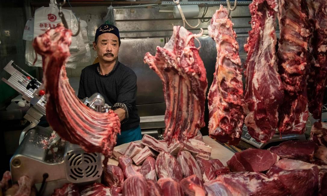 Açougueiro corta carne em sua barraca em um mercado de Pequim Foto: NICOLAS ASFOURI / AFP