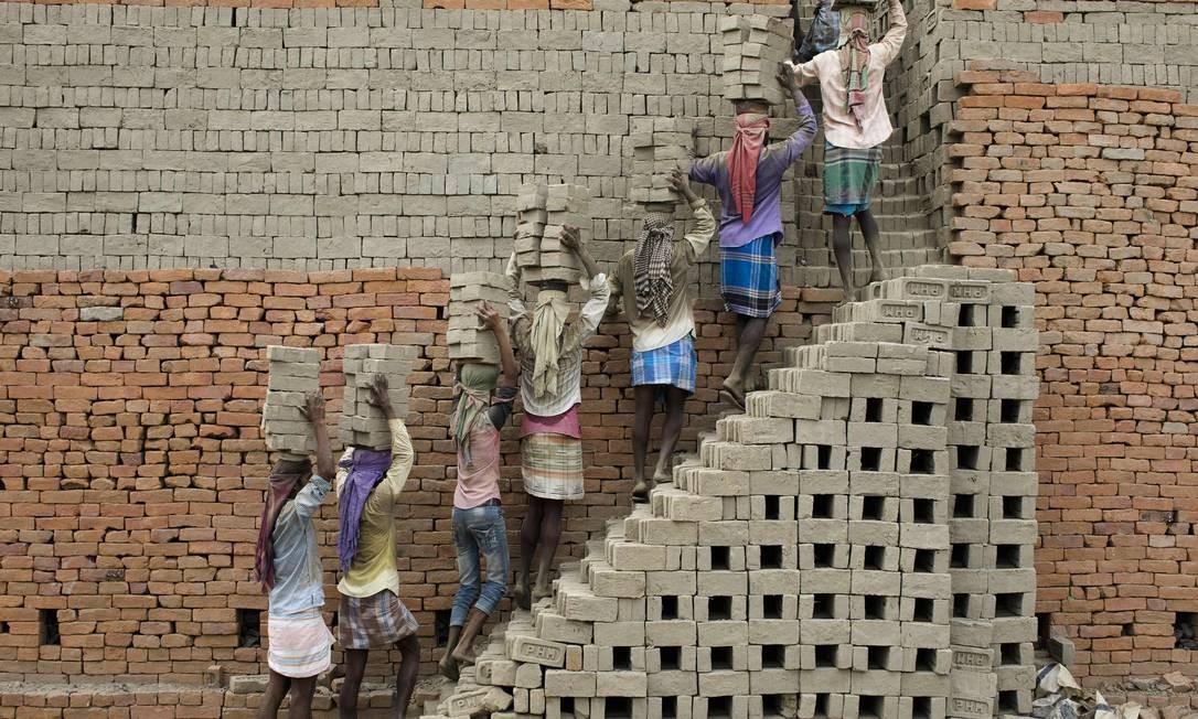 Trabalhadores indianos carregam tijolos de barro para um forno de tijolos em Farakka, no estado indiano de Bengala Ocidental Foto: XAVIER GALIANA / AFP