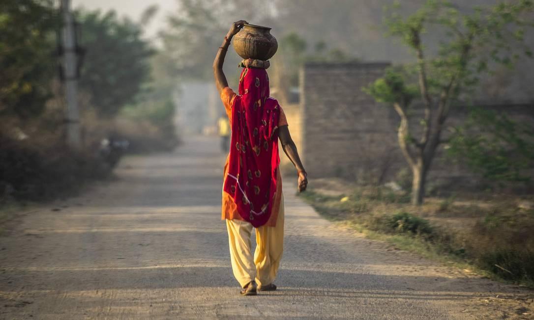 Uma mulher indiana caminha enquanto segura um jarro com água na cabeça, em uma vila de Mohatabad, nos arredores de Faridabad, no norte do estado indiano de Haryana Foto: MONEY SHARMA / AFP