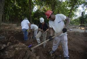 Arqueóloga avalia peças no meio da escavação Foto: Alexandre Cassiano / Agência O Globo