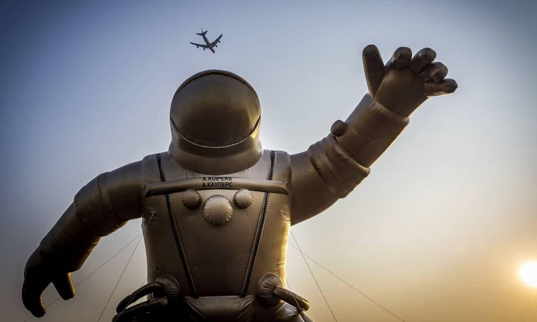 Uma aeronave voa alto sobre um astronauta inflável gigante dourado, representando o astronauta holandês Andre Kuiper, para marcar o início da quinta Semana Nacional de Museus em Sassenheim. Kuipers usou a roupa de pressão russa em 2004 durante sua aventura espacial com a cápsula russa Soyuz Foto: LEX VAN LIESHOUT / AFP
