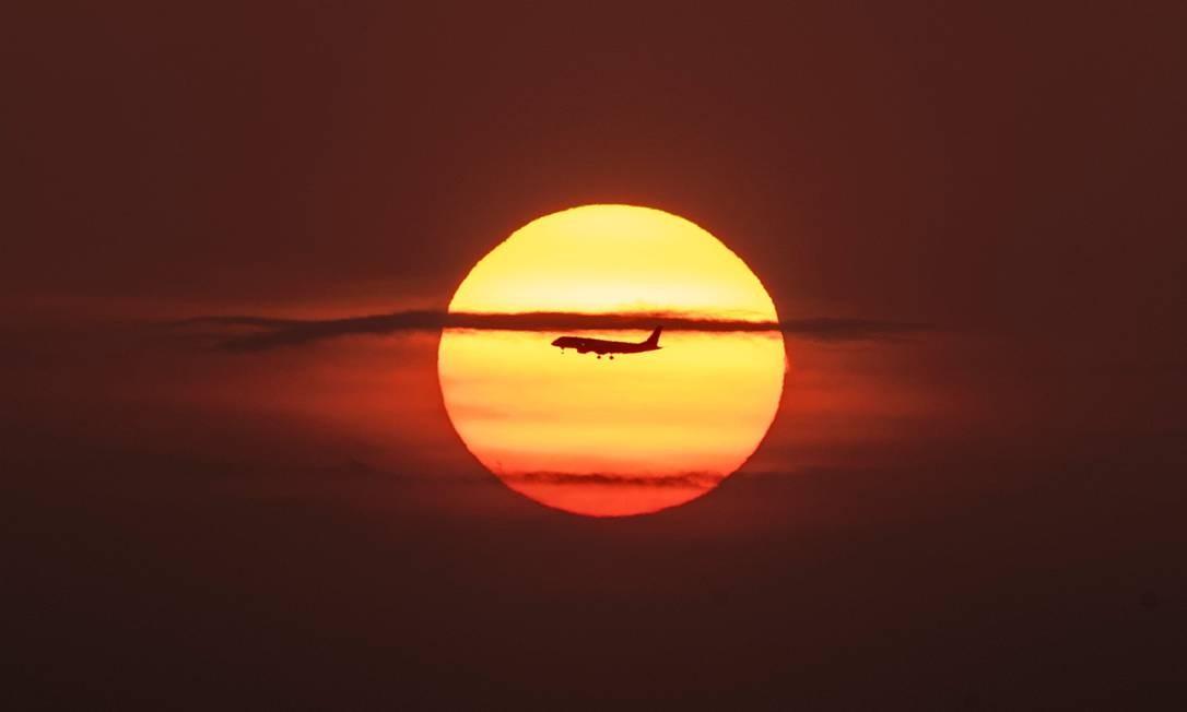 Um avião sobrevoa a Baía do Panamá, na Cidade do Panamá, durante o nascer do sol Foto: LUIS ACOSTA / AFP