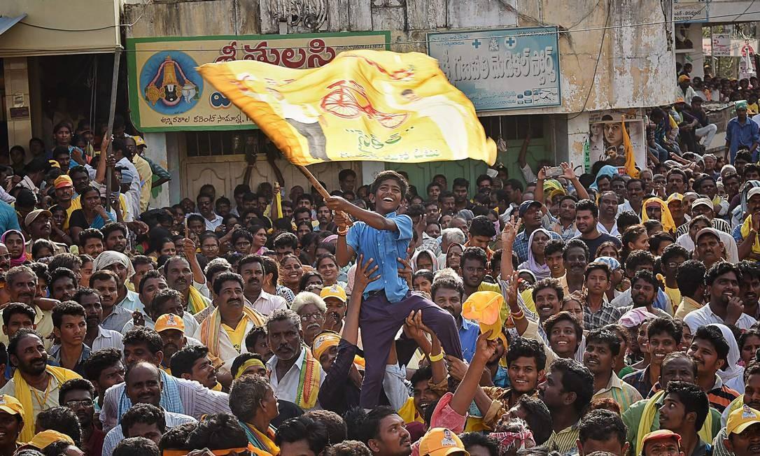 Um jovem partidário do Telugu Desam Party (TDP) agita uma bandeira de N. Chandrababu Naidu, ministro-chefe do estado indiano de Andhra Pradesh e ex-primeiro-ministro. H.D. Deve Gowda discursa em um comício público no distrito de Krishna, no estado indiano de Andhra Pradesh. A Índia realizará suas eleições gerais, que duram quase seis semanas, a partir de 11 de abril, quando centenas de milhões eleitores votarão na maior democracia do mundo Foto: STR / AFP