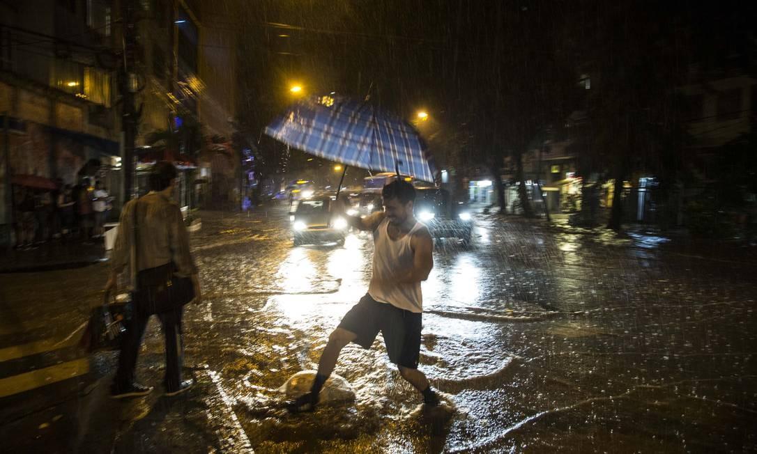 Em Laranjeiras, um pedestre tenta atravessar a rua, totalmente alagada Foto: Guito Moreto / Agência O Globo