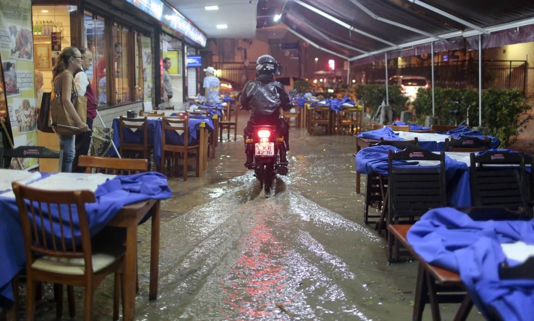 Motociclista tenta fugir do alagamento através da calçada de um restaurante em Copacabana Foto: Bruno Kaiuca / Agência O Globo