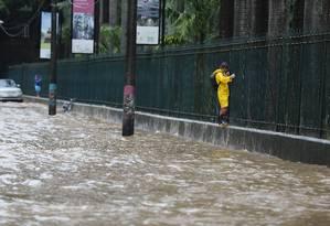 Com a via totalmente alagada, homem anda em mureta do Jardim Botânico Foto: Pablo Jacob / Agência O Globo