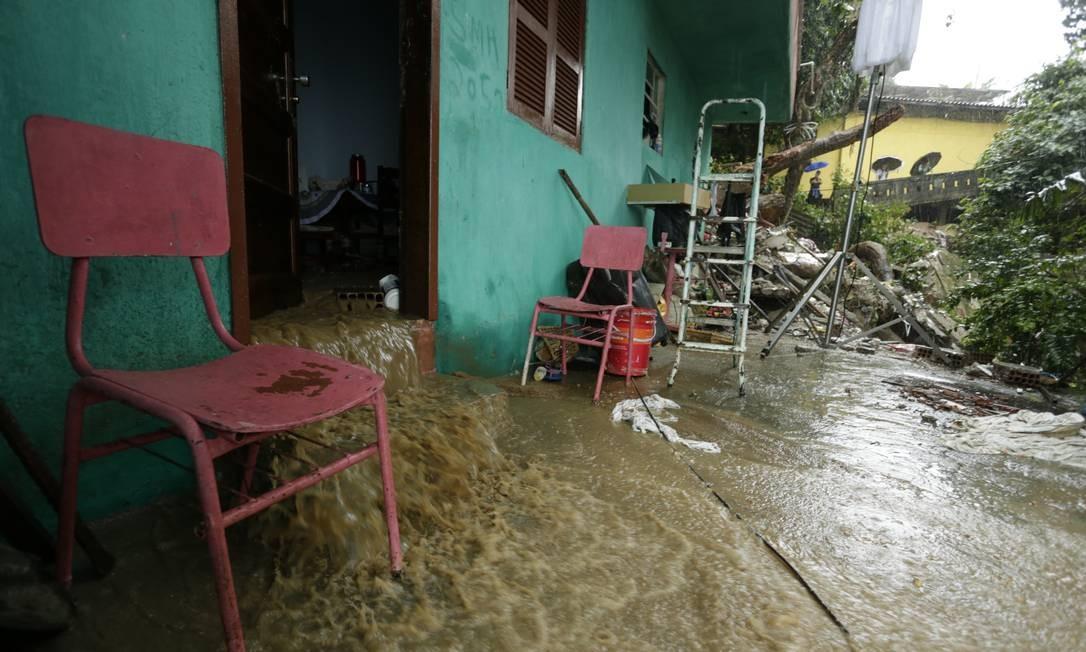 Muita água escoa de dentro de uma das casas no Morro da Babilônia, no Leme Foto: Gabriel Paiva / Agência O Globo