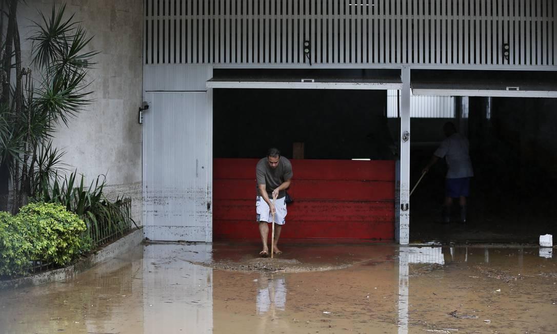 Hhomem tentar retirar água da entrada de um prédio na Avenida Borges de Medeiros, na Lagoa Foto: Pablo Jacob / Agência O Globo