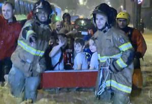 Bombeiros puxam barco com grupo de meninos resgatados, perto da Rua Pacheco Leão Foto: TV Globo / Reprodução