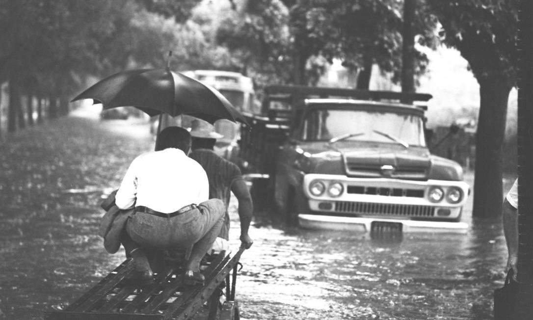 Homem sobe em carrinho de outro para escapar do alagamento na Rua Teodoro da Silva, Grajaú, Rio de Janeiro, em enchente de 1968 Foto: Agência O Globo