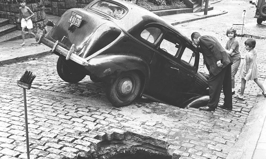Carro preso em buraco na rua, aberto pela enchente em 1962, no Rio de Janeiro Foto: Agência O Globo