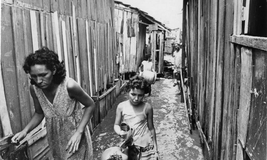 Família caminha durante enchente na favela da Maré, 1979 Foto: Agência O Globo