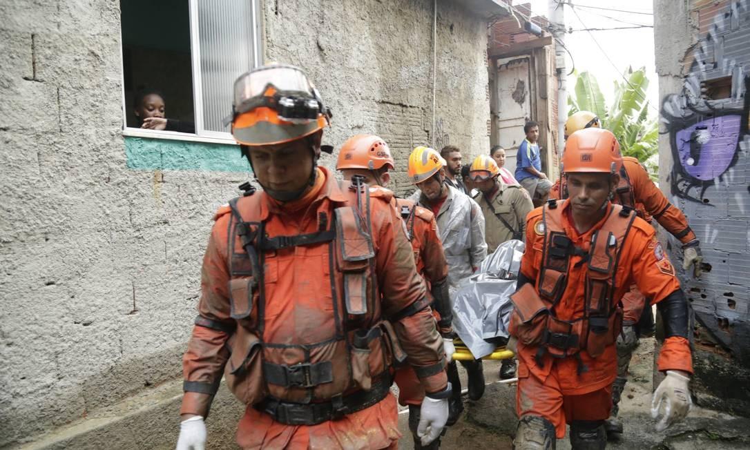 Após horas de buscas, bombeiros retiram o corpo de Gilson Cezar, que estava desaparecido após deslizamento desde a noite de segunda-feira no Morro da Babilônia Foto: Gabriel Paiva / Agênci a O GLOBO