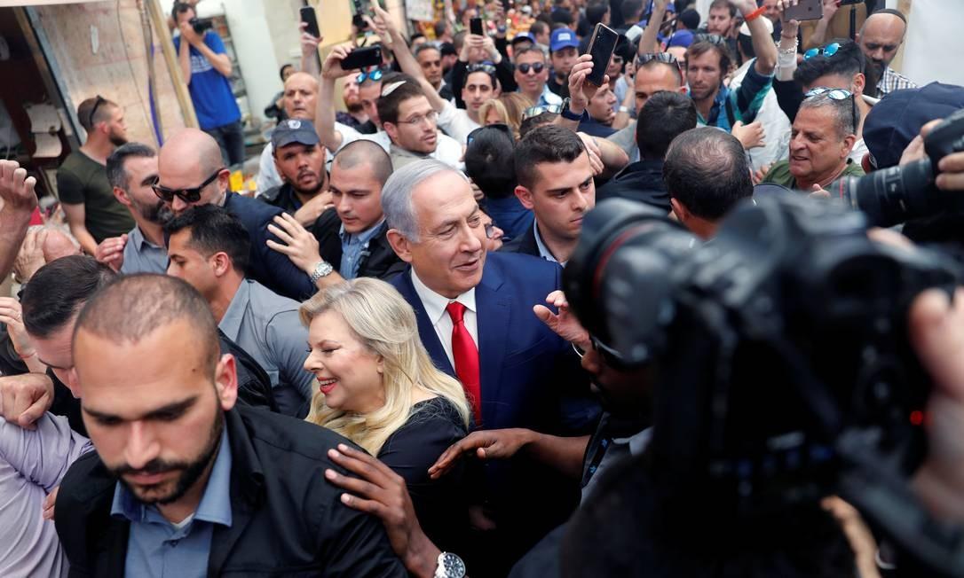 Cercados por seguranças, o primeiro-ministro israelense, Benjamin Netanyahu, e sua mulher, Sara, visitam mercado em Jerusalém Foto: RONEN ZVULUN 08-04-2019 / REUTERS