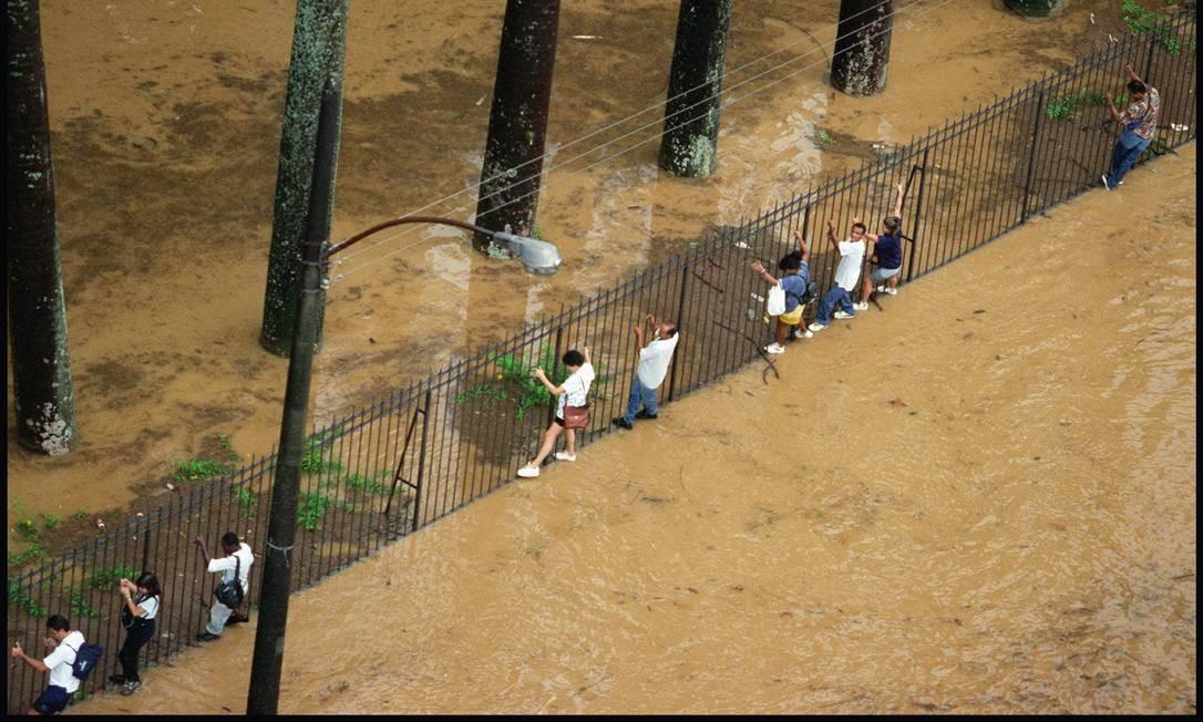 Pedestres são obrigados a usar as grades do Jardim Botânico, em 1996 para escapar da água que cobriu a rua com nome do bairro Foto: Márcia Foletto / Agência O Globo