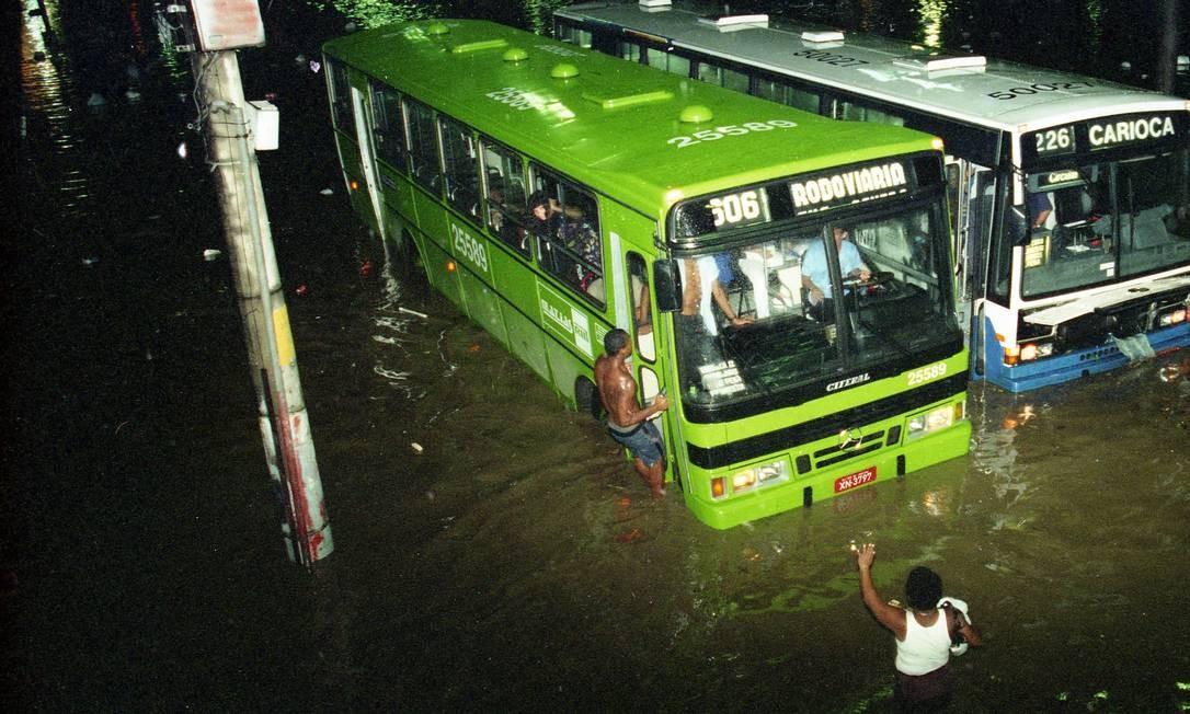 Dez anos depois, outra grande enchente atinge a Praça da Bandeira, em janeiro de 1996, deixando ônibus presos. Pedestres tentam entrar em veículo para se proteger do temporal e do alagamento Foto: Julio Cesar Guimarães / Agência O Globo