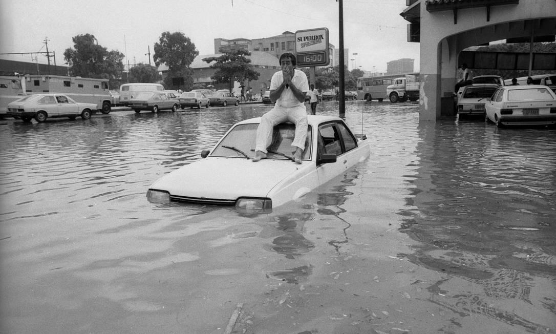 Fevereiro de 1986. Motorista espera a água da chuva baixar sentado sobre o teto de seu carro, na Praça da Bandeira Foto: Anibal Philot / Agência O Globo