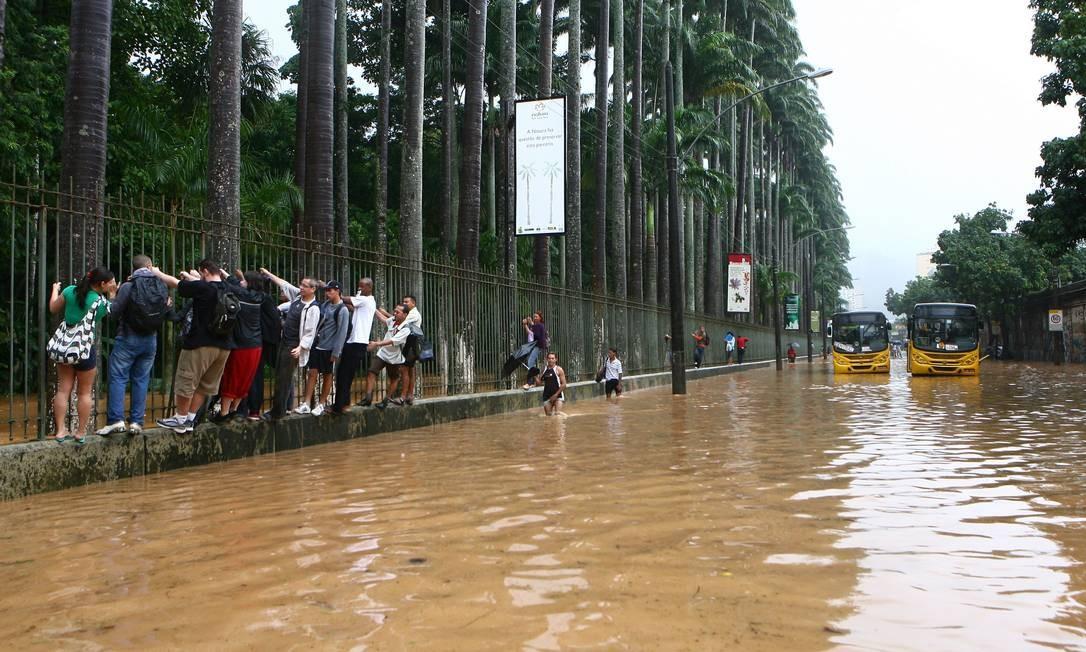 Cena que se repete. Em abril de 2010, na Rua Jardim Botânico, pedestres cruzam a via alagada nas grades do Jardim Botânico Foto: Marco Antônio Cavalcanti / Agência O Globo