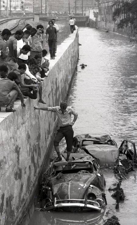 Dono fica sobre carro totalmente destruído no Rio Maracanã durante enchente de março de 1971 Foto: Eurico Dantas / Agência O Globo