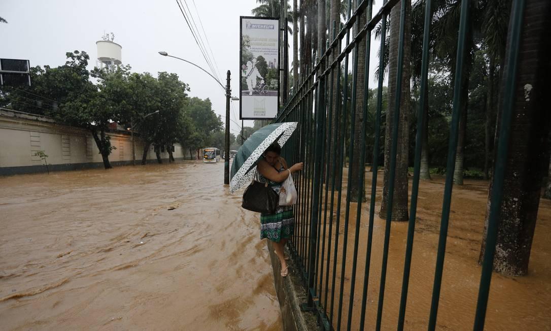 Em 9 de abril de 2019, o último grande temporal que atingiu o Rio e a mesma cena de décadas. Uma mulher caminha pela mureta do Jardim Botânico para fugir da água da chuva Foto: Pablo Jacob / Agência O Globo