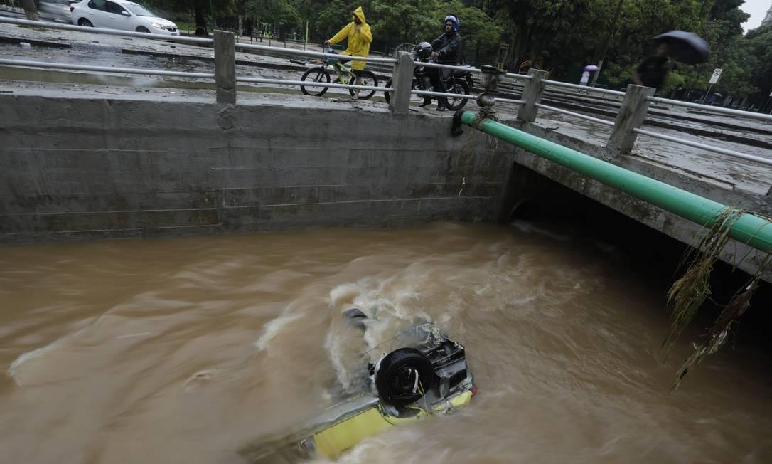 Durante o último temporal, carro cai dentro do Rio Maracanã, próximo à Rua Doutor Otávio Kelly, e fica de cabeça para baixo Foto: Custódio Coimbra / Agência O Globo