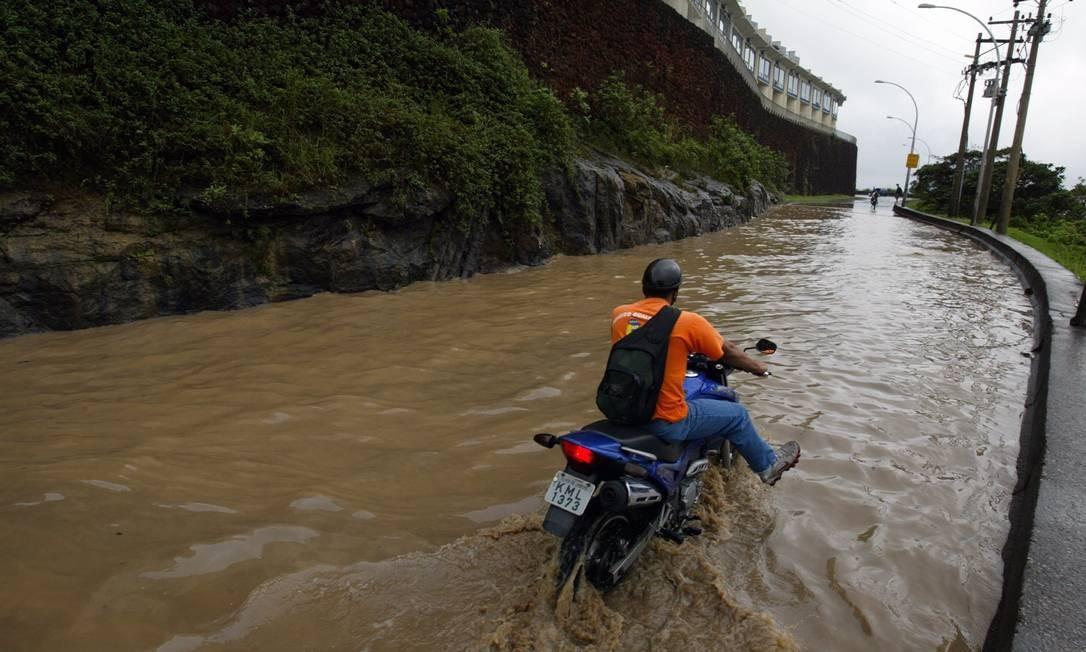 Em outubro de 2005, motocilista atravessa a Avenida Niemeyer, em São Conrado, coberta pela água da chuva Foto: Custódio Coimbra / Agência O Globo