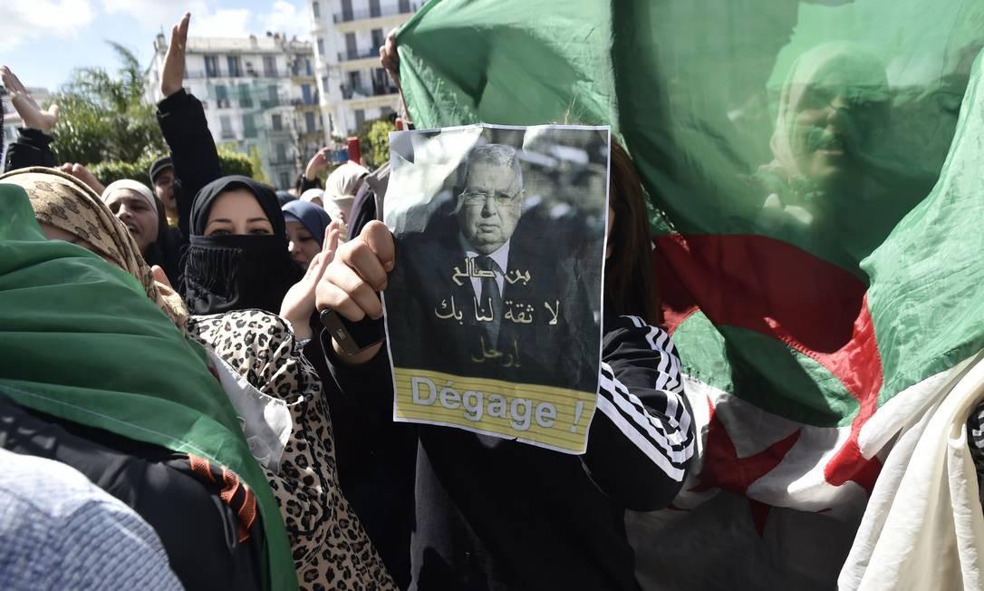 """Um manifestante argelino segura um cartaz com uma foto do presidente interino, Abdelkader Bensalah, com a frase em árabe e francês: """"Bensalah sai, não confiamos em você"""", durante uma manifestação contra o sistema na capital, Argel. Parlamentares argelinos nomearam Bensalah, um dos líderes do regime, como o primeiro novo presidente do país em duas décadas. Manifestantes buscam mudanças radicais após a renúncia do veterano líder Abdelaziz Bouteflika Foto: RYAD KRAMDI / AFP"""