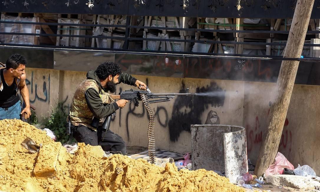 Um combatente líbio, leal ao Governo do Acordo Nacional (GNA), dispara uma metralhadora durante confrontos com forças leais a Khalifa Haftar, ao sul do subúrbio de Ain Zara, capital de Trípoli Foto: MAHMUD TURKIA / AFP