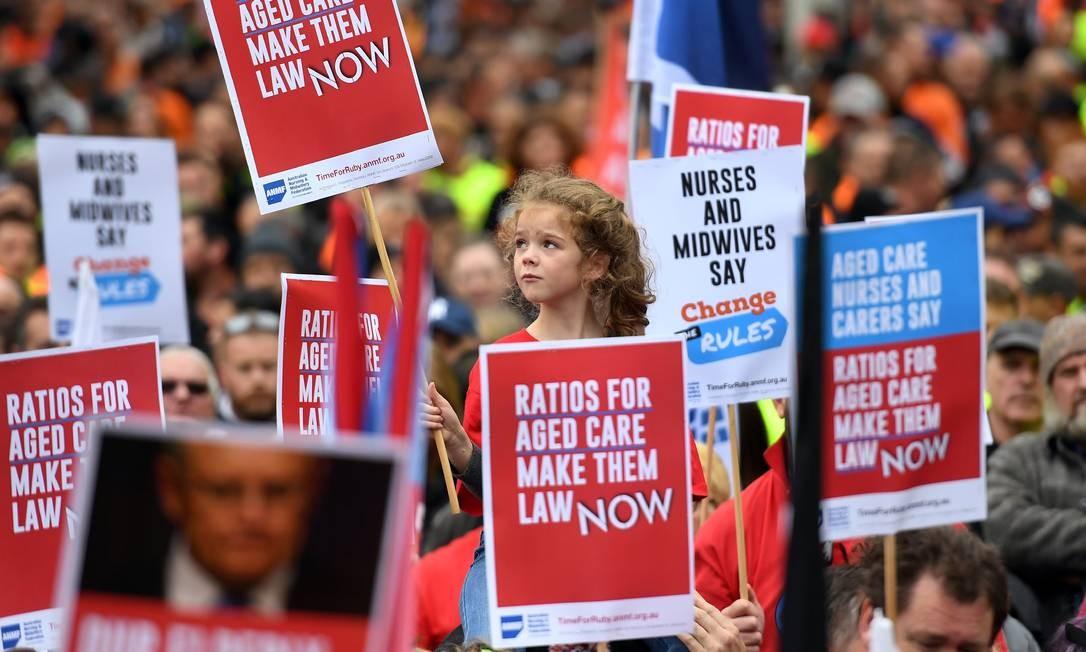 Pessoas participam de uma marcha por melhores condições de trabalho e salários mais altos na Austrália, em Melbourne Foto: WILLIAM WEST / AFP