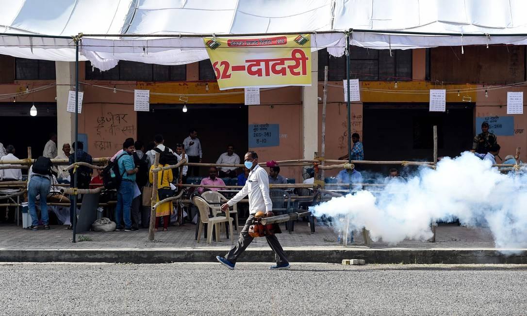 Um trabalhador municipal indiano lança uma fumaça para repelir mosquitos em um centro de distribuição de material eleitoral em Noida Foto: MONEY SHARMA / AFP