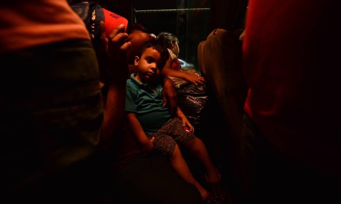 Uma criança hondurenha e sua mãe são vistos em um ônibus saindo do Centro Metropolitano de San Pedro Sula, a 300 quilômetros ao norte de Tegucigalpa, para viajar à fronteira com a Guatemala Foto: ORLANDO SIERRA / AFP