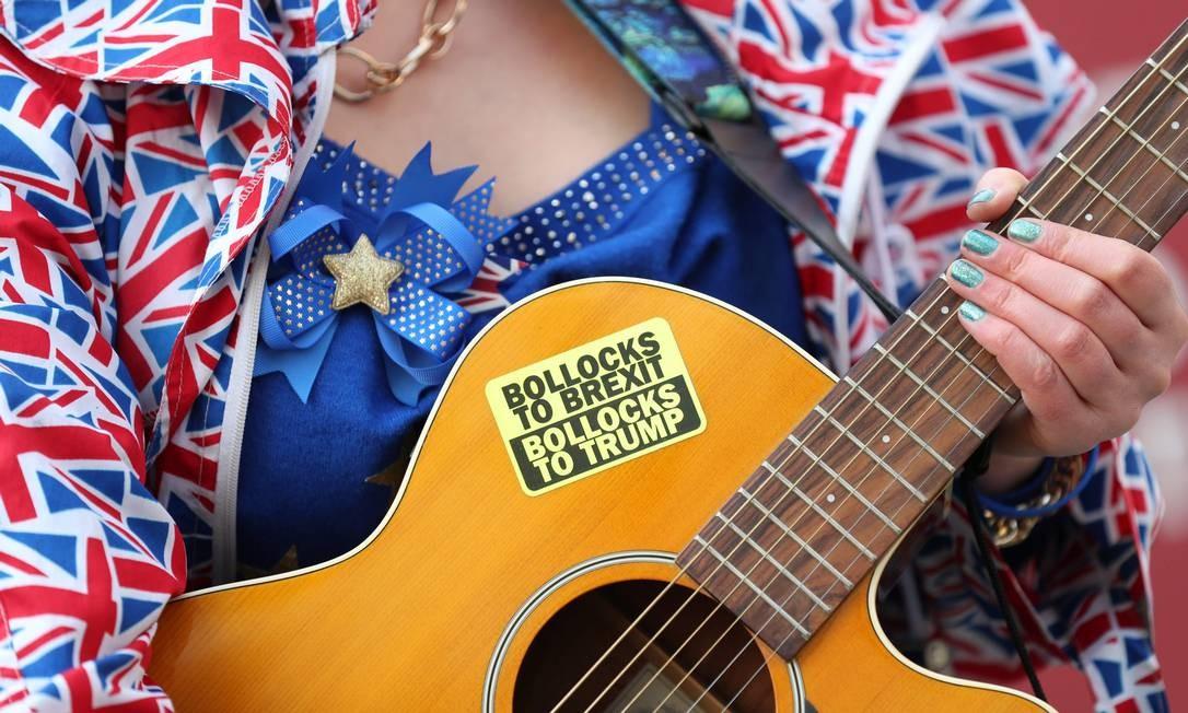 Uma mulher se apresenta com um violão durante protesto antes da reunião do Conselho Europeu sobre o Brexit no Edifício Europa, no Parlamento Europeu, em Bruxelas Foto: KENZO TRIBOUILLARD / AFP
